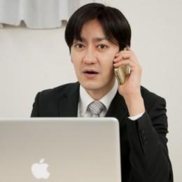パソコンを操作しながら電話対応する男性