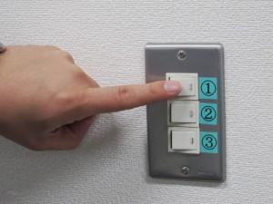 壁のスイッチを押そうとしている手