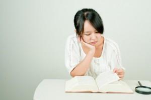 頬杖をついて本をめくっている女性
