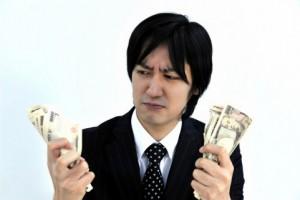 お金を持って悩んでいる男性
