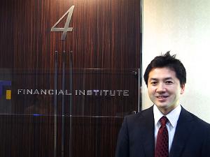 株式会社フィナンシャル・インスティチュートの社名ロゴを背景に立つ川北氏の写真