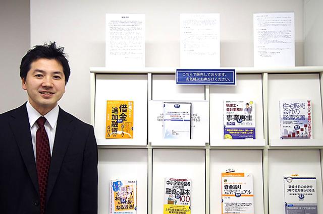販売する本と川北氏の写真