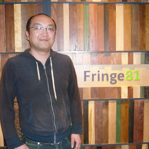 Fringe81株式会社のロゴを背景に立つ田中弦氏の写真
