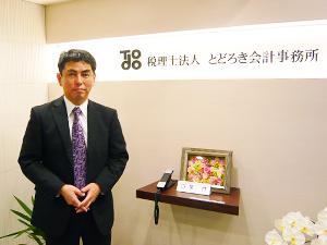 税理士法人とどろき会計事務所のロゴを背景に立つ轟勝之氏の写真