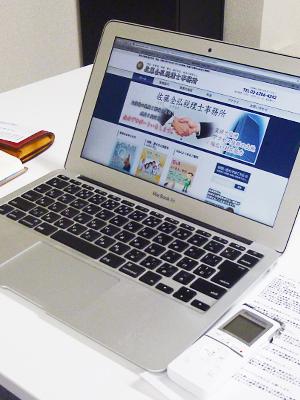 佐藤全弘税理士事務所ホームページを開いているノートパソコン