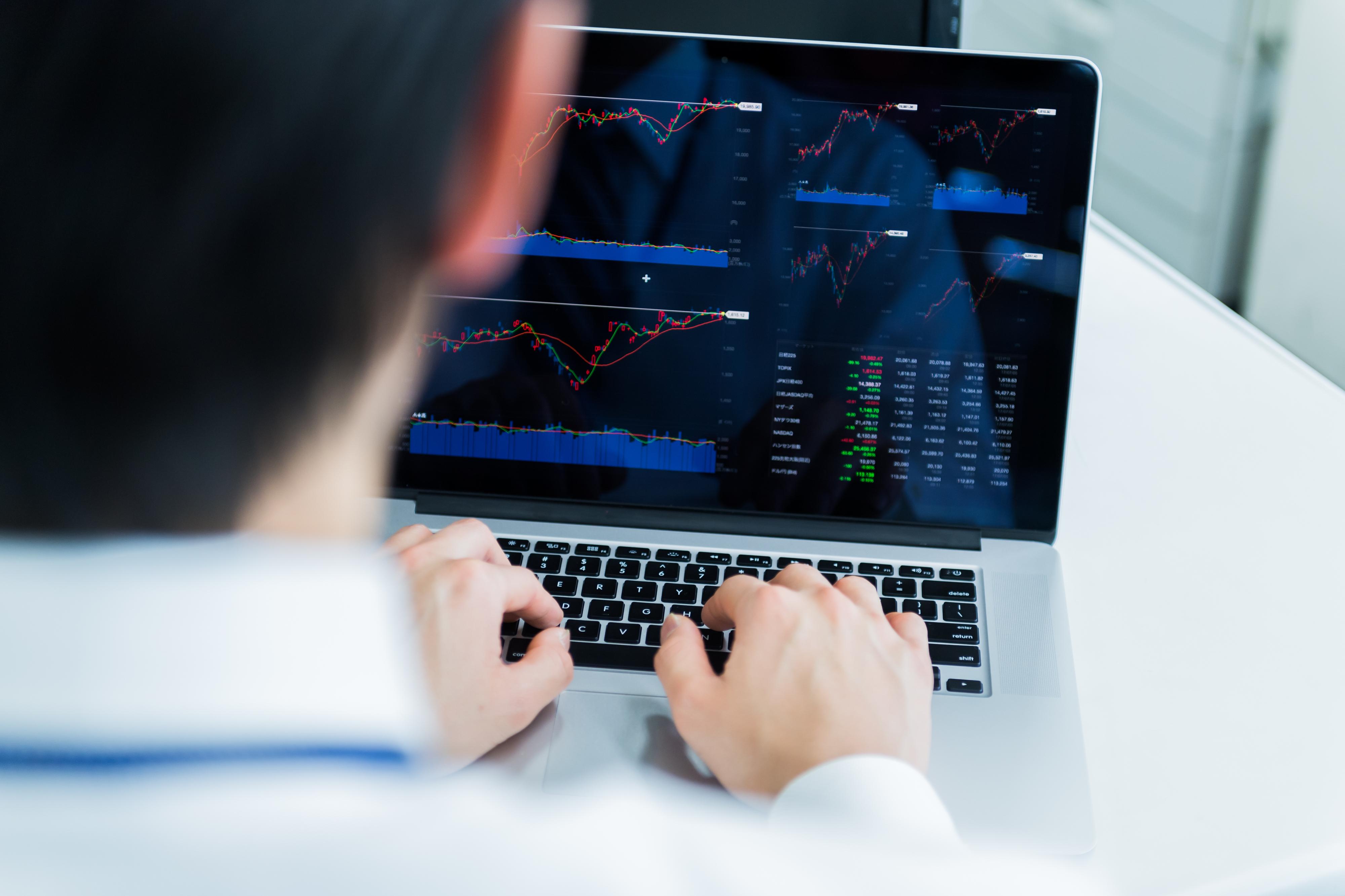 チャートをパソコンで見ている男性