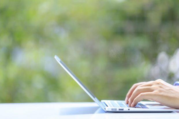 野外でパソコンを操作する人