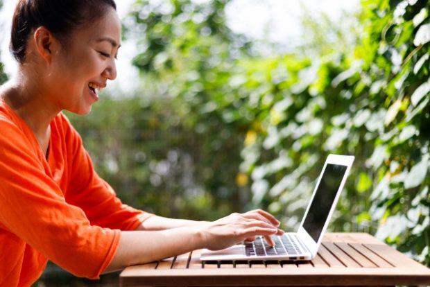 野外で楽しそうにパソコンを操作する女性