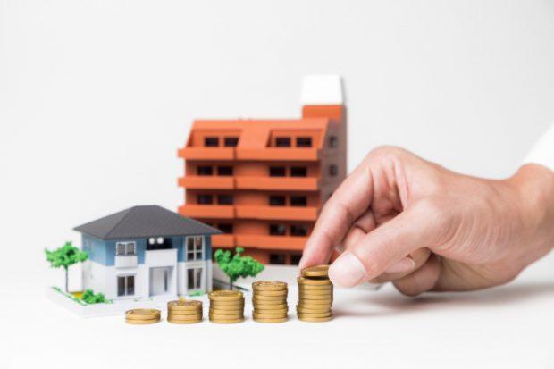 住宅とマンションの模型の前でコインを積み上げる