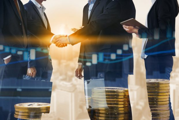 ビジネスマン同士の握手と積み重なるコイン