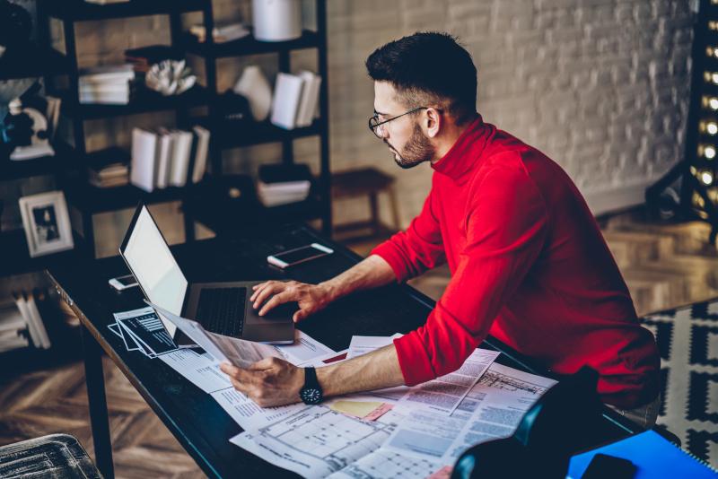 インターネットを使用してコンピューター上のウェブサイト情報をチェックする眼鏡で物思いにふけるひげを生やした男