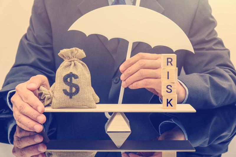 ビジネスマンが白い傘を握り、基本的なバランススケールでドルの袋を保護し、詐欺や詐欺からお金を守る