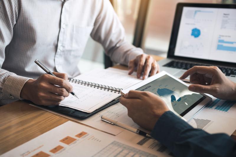 オフィスルームで予算会議中に財務計画のグラフと会社を議論する2つのビジネスパートナーシップの同僚