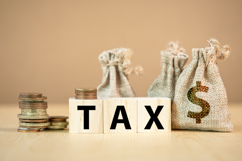 Tax wording on wooden cubes with US dollar coins and bag