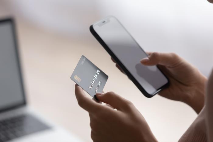 キャッシュカードを見ながらスマートフォンを操作する女性の手